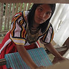 Weaving some cloth using a wooden loom.