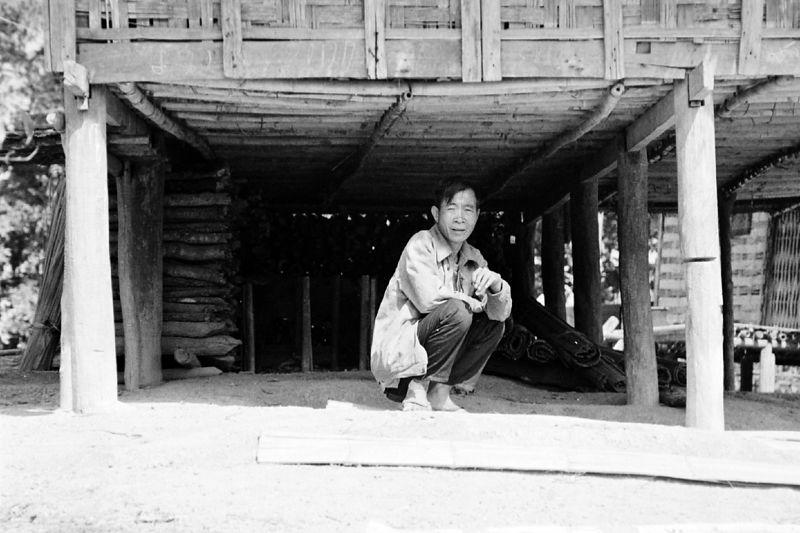 man squatting under house