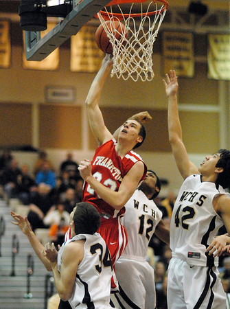 Frankton junior guard Aaron Korn drives past Winchester defenders to post two points on the scoreboard for the eagles.