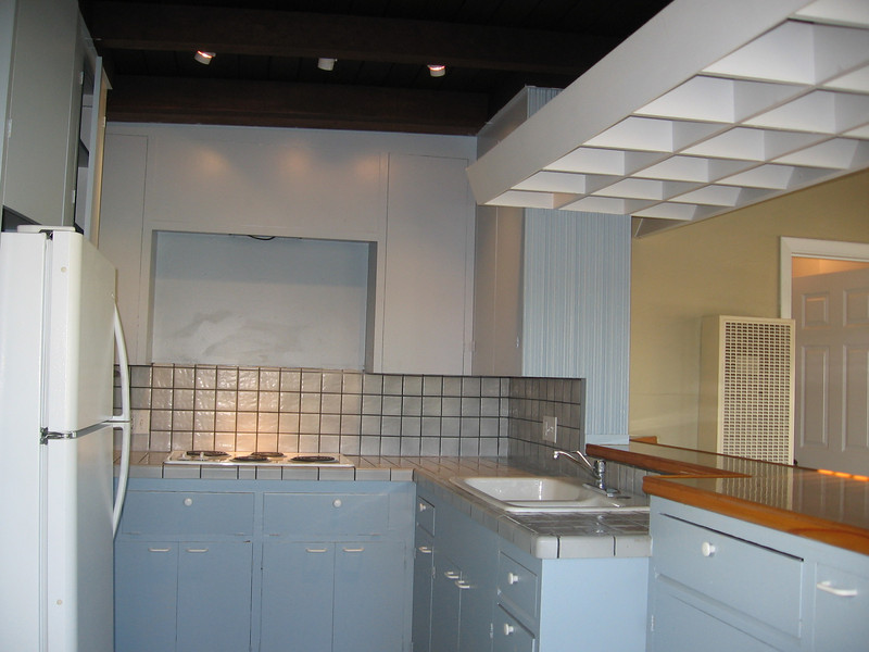 Kitchen with refrigerator, oven and cooking surface unit