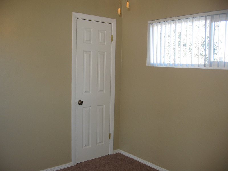 Second bedroom showing closet and window with new vertical blinds