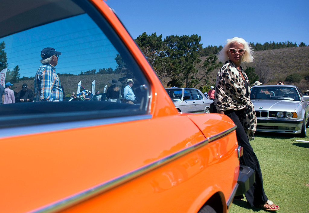 . Marianne Leiven walks past Don Swiers 1974 2002 Tii BMW Friday, August 16th, 2013 at the Legends of the Autobahn car show at Rancho Canada Golf Course. (Matthew Hintz/Monterey County Herald)