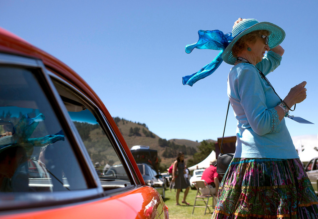 . Emily Woollett\'s hat nearly comes off in a gust of wind, Friday, August 16th, at the Legends of the Autobahn car show at Rancho Canada Golf Course. (Matthew Hintz/Monterey County Herald)