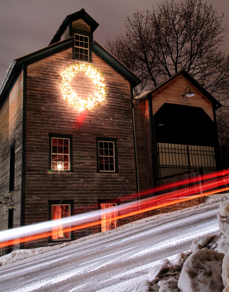 Car passing down the hill at night in front of the Lemont Granary
