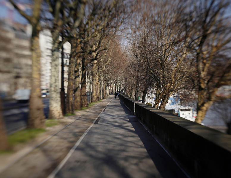 A sidewalk alongside the Seine River in Paris extends into the distance. Note that this image shows the lens blur effect that comes with a Lensbaby.