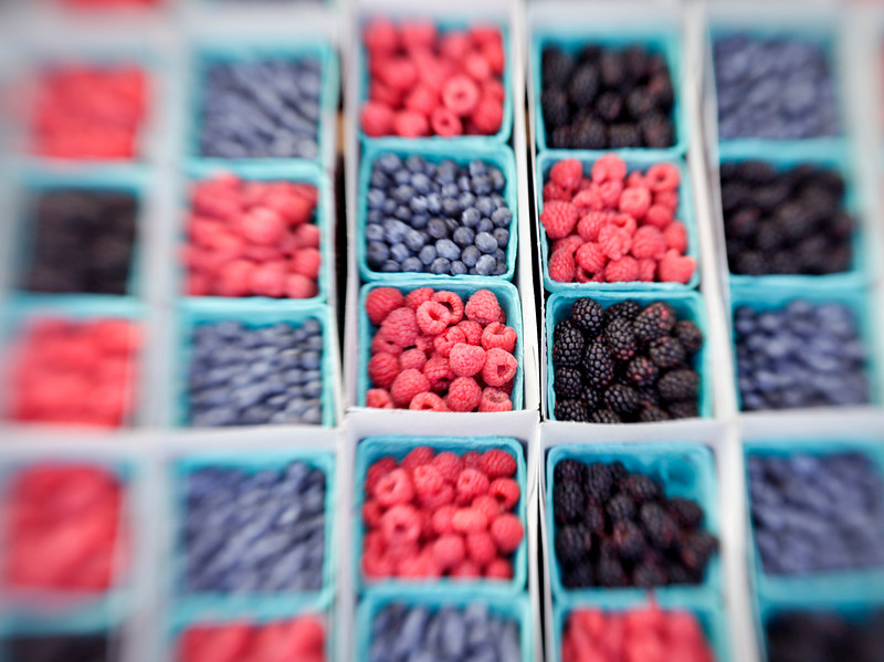 Baskets of raspberries, blueberries, blackberries and strawberries on display in a market. The colors contrast throughout the checkerboard-like pattern. Note that this image is sharp in the center but blurs progressively towards the edges