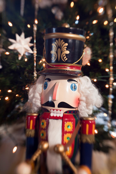 A traditional wooden nutcracker toy soldier playing a drum is a decoration in front of a Christmas Tree to provide some holiday spirit. A special lens effect blurs the outside of the image to add an element of dreaminess and separation from reality.