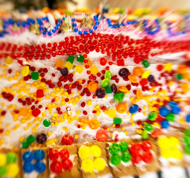 A psychadelic riot of colorful candy scattered on the roof of a gingerbread house at a Christmas display. Special lens effect is intentional to emphasize the dreamy nature of the display.