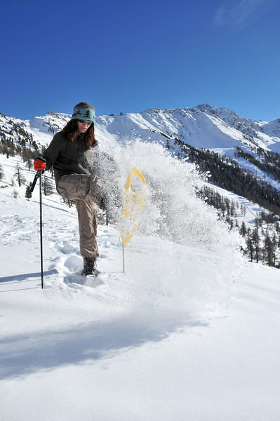 Nendaz, Tracouet<br /> girl with snow shoes sending a cloud of powder snow in the air<br /> promenade en raquettes de neige