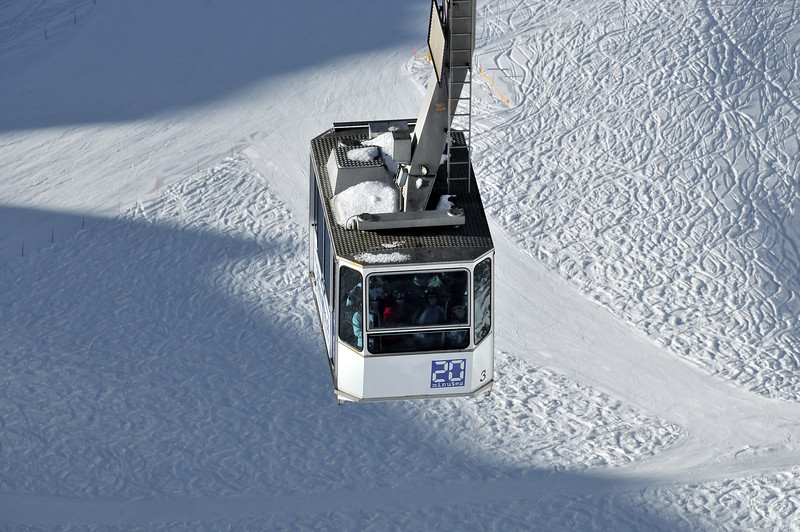 Skiing. Cable car full of skiers above a glacier with tracks in the snow