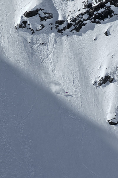 a woman snowboarder in the 2009 womens extreme freeride finals lands after a jump over a cliff and followed by a stream of snow