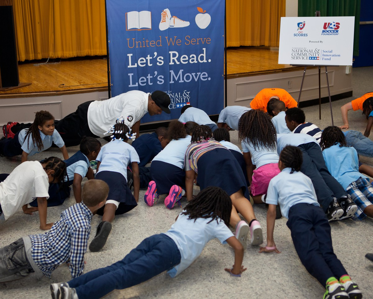 Second graders at Garfield Elementary School in Washington, DC, perform push-ups with NFL player Visanthe Shiancoe during a Let's Read. Let's Move. event at the school on May 29, 2013. (Corporation for National and Community Service Photo)