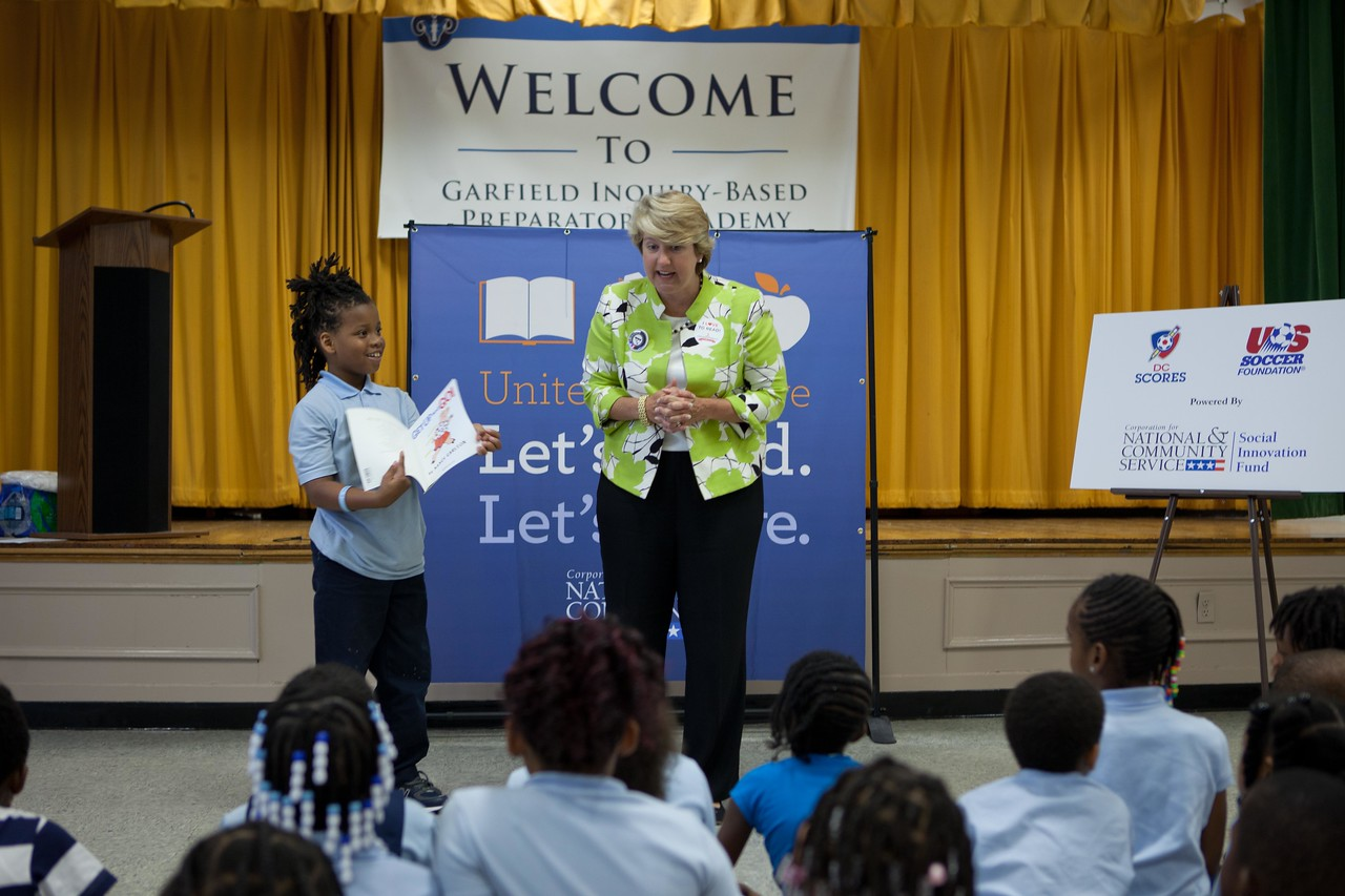 CNCS CEO Wendy Spencer gets help from a student as reads to children at Garfield Elementary School during a Let's Read. Let's Move. in Washington, DC. (Corporation for National and Community Service Photo)