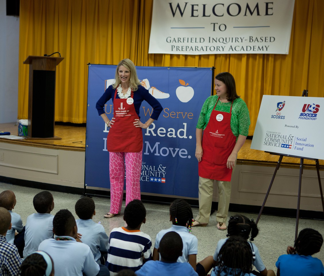 """Junior League of Washington President Wendy Cumberland talks to second graders at Garfield Elementary about the book giveaway during the Let's Read. Let's Move. event at the school on May 29, 2013."""" alt=""""Junior League of Washington volunteers talk to second graders at Garfield Elementary about the book giveaway during the Let's Read. Let's Move. event at the school on May 29, 2013. (Corporation for National and Community Service Photo)"""