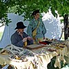 "Sgt. Patrick Gass of the Lewis & Clark Expedition sewing ""mockersins"" (Clark's spelling) at the Lewis & Clark Days, Walla Walla, WA, June 4, 2005.  George Gibson is looking on.  Notice all the skins, pelts, antlers, etc to be worked on."