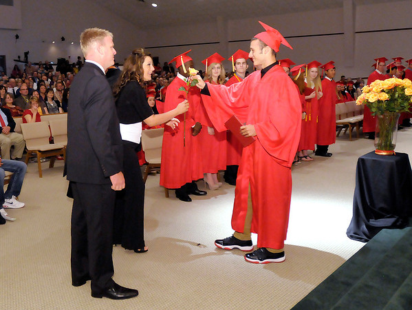 Austin Castor gives his mother a rose after receiving his diploma during Liberty Christian's graduation at Bethany Christian Church on Saturday.