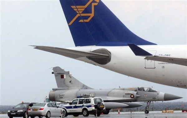 A Qatar Air Force fighter jets on the ground next of a Cyprus airways plane at Larnaca international airport, Cyprus, Tuesday, March 22, 2011. Two Qatar Air Force fighter jets and a cargo aircraft were heading to Crete Tuesday in the first sign of military operations by Qatar so far to help enforce a no-fly zone over Libya, officials said. The planes made an unscheduled stop at the island's Larnaca airport, and government spokesman Stefanos Stefanou said in a statement that the two Mirage jets and one cargo aircraft would depart after refueling. (AP Photo/Christos Thedorides)