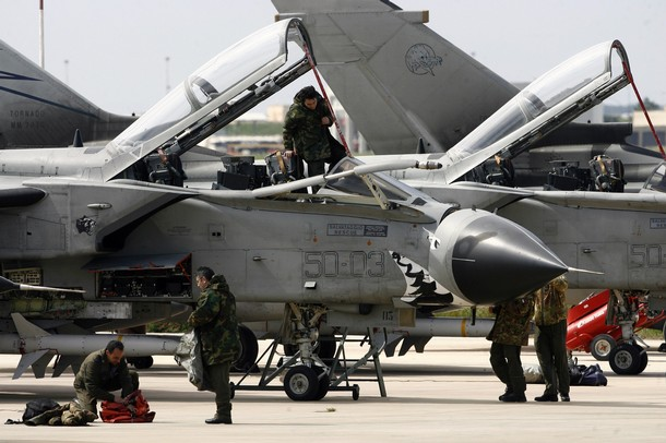 """Technician prepare a Tornado jet fighter of the Italian airforce on March 21, 2011 at Trapani-Birgi airbase in Sicily. Western and Arab warplanes are converging on Italy's air bases, including the one of Trapani-Birgi, to join the international campaign to cripple the ability of Moamer Kadhafi's forces to attack Libyan civilians in the UN-mandated Operation """"Odyssey Dawn"""" with air strikes on Libya.   AFP PHOTO / MARCELLO PATERNOSTRO (Photo credit should read MARCELLO PATERNOSTRO/AFP/Getty Images)"""