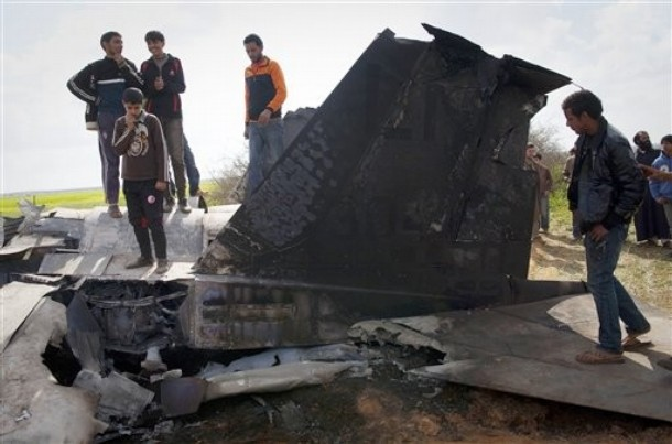 Libyans inspect the tail section of a US  F15 fighter jet after it crashed in an open field in the village of  Bu Mariem, east of Benghazi, eastern Libya, Tuesday, March 22, 2011, with both crew ejecting safely. The U.S. Africa Command said both crew members were safe after what was believed to be a mechanical failure of the Air Force F-15. The aircraft, based out of Royal Air Force Lakenheath, England, was flying out of Italy's Aviano Air Base in support of Operation Odyssey Dawn.(AP Photo/Anja Niedringhaus)