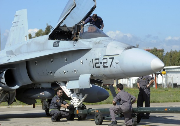 Spanish ground crew work on an F-18 jet fighter plane at the NATO airbase of Decimomannu, in the southern Italian island of Sardinia, March 20, 2011. NATO ambassadors approved an operations plan for the alliance to help enforce a U.N. arms embargo on Libya on Sunday, a NATO statement said. Picture taken on March 20, 2011.<br />   REUTERS/Stringer ( ITALY - Tags: POLITICS MILITARY CONFLICT)