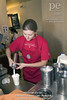 TA9.6 / Photo of barista making coffee drink or spot photo of coffee drink<br /> <br /> Choice 10 of 14<br /> <br /> White young female Starbucks employee wearing red apron prepares coffee order for customer