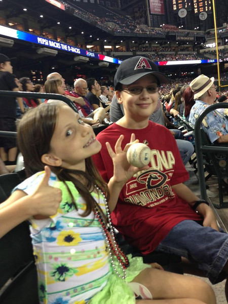 Friday, July 26, 2013 - Caroline and David Rossington celebrating a game ball toss up from a Diamondback walking off the field.