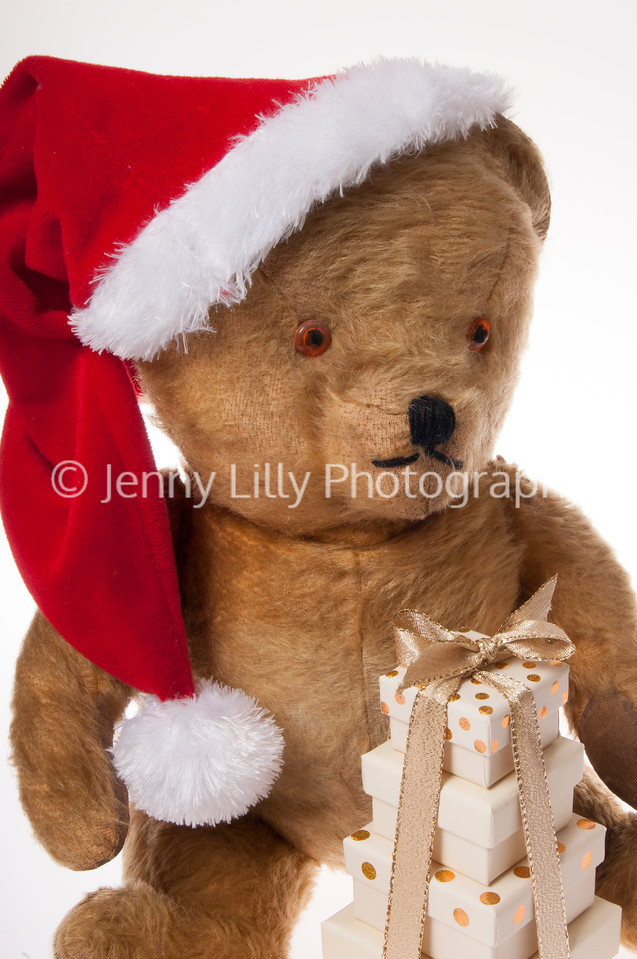 Vintage teddy bear wearing a Santa hat with presents isolated on white background