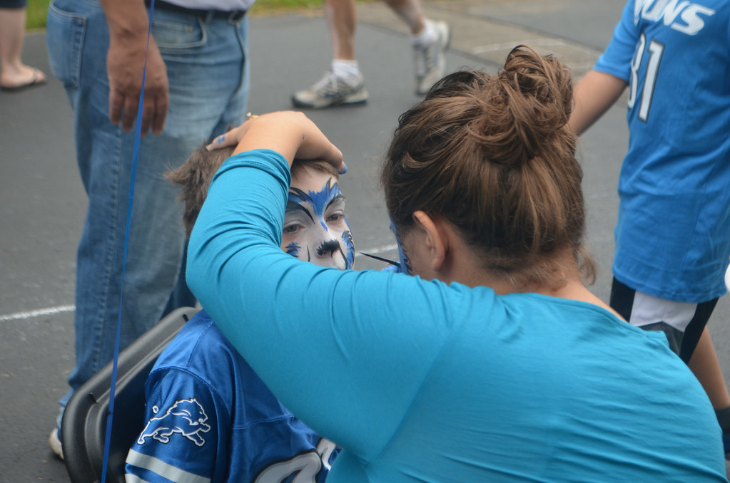 . Auburn Hills resident Carl Tisler, 10, gets a lion painted on his face prior to a Detroit Lions open practice Aug. 2.  Photo by Dave Herndon.