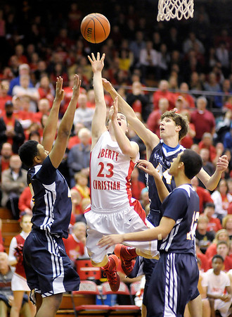 Don Knight / The Herald Bulletin<br /> Liberty Christian's Ben Bowen shoots while surrounded by Marquette Catholic's defense in the 1A semi-state at Lafayette Jefferson on Saturday.