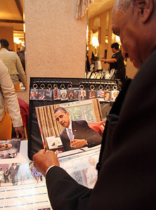 Carlton Larkins of Elyria, checks out a president Obama calendar for sale at the Old School Lorain Groove inauguration party.   photo by Ray Riedel