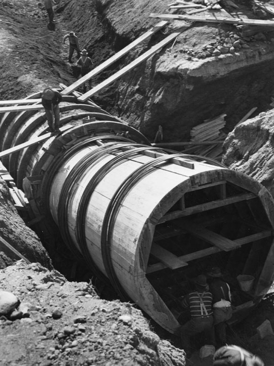 . A view of early pipe used for building the L.A. Aqueduct to Owens Valley, done between 1907 and 1913. The aqueduct was considered the 2nd greatest engineering accomplishment of its age, after the Panama Canal. Here men are working with a large pipe being buried in a trench. (1910)  (Los Angeles Public Library)