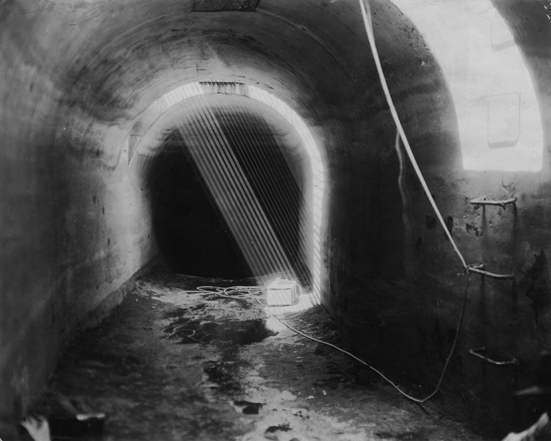 . Photo shows a box of dynamite in the Los Angeles aqueduct, which led investigators to discoveries which will result in many arrests. The dynamite was let down by a rope through a manhole and was expected to float into No Name siphon, and explode there, but it failed to go off despite waterproof fuses and electric contact. Photo dated: February 22, 1928.  (Los Angeles Public Library)