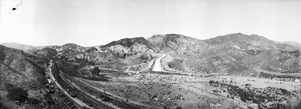 . (November 5, 1913) - Water can be seen running down the aqueduct at center amongst mountains. It curves at center to the right. People can be seen scattered in the flat, valley area at center in front of the aqueduct, while cars can be seen parked alongside the road at left. Mountains run across the background.  (USC)
