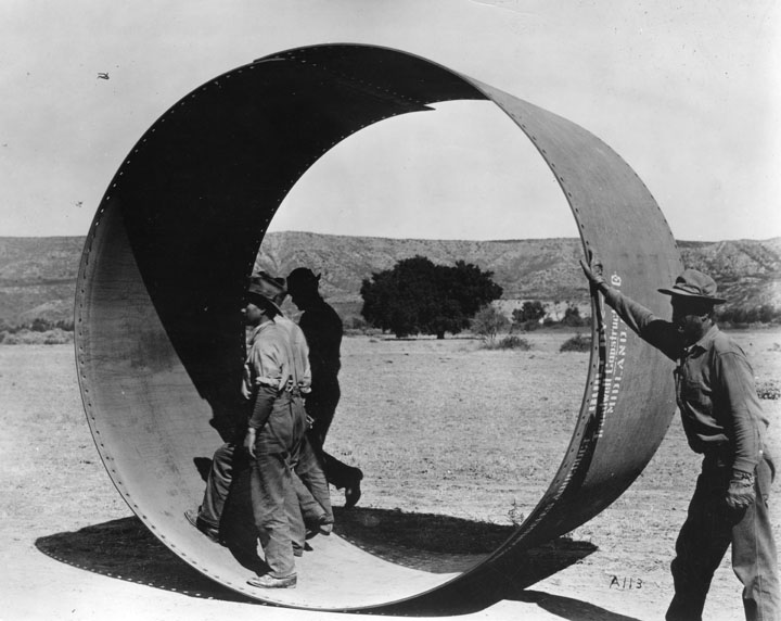 . Three men stand inside one section of pipe to be used on the L.A. Aqueduct--one man stands outside. The pipe section is at least twice as high as the men standing inside. It was built by Treadwell Construction Co., Midland.   (Los Angeles Public Library)