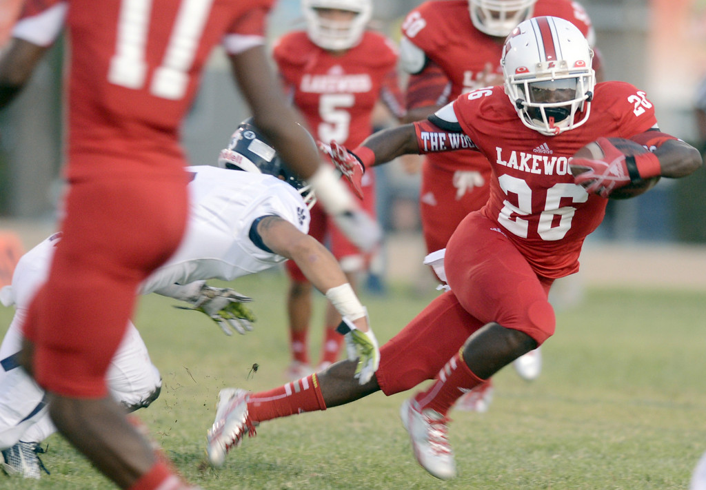 . Lakewood\'s Jason Floyd(26) attempts to avoid tackles as he looks for yards against Loyola during a game in Lakewood CA. Friday September 3, 2013.  (Photo by Thomas R. Cordova/ Daily Breeze)