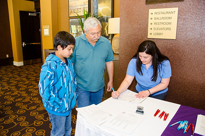 Daphne Phillips assists Alan Odell and son Annant, 10, at the Membership table in Lubbock.