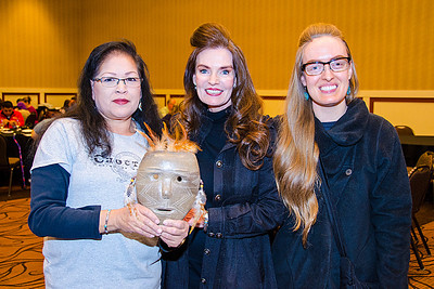 Rita Jo Fitzgerald, center, and daughter Mary Elizabeth Allred are pleased with the pottery mask they purchased from artist Evangaline Robinson.