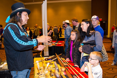 Les Williston shows off Choctaw weaponry to Valerie Montez and children Natalie, 10, and Christopher, 7 at the Lubbock gathering.