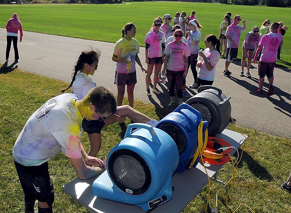 Pat Christman <br /> Runners blow the excess powdered dye off of themselves after Saturday's Color Rush 5k race at MSU.