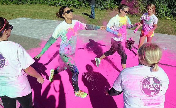 Pat Christman <br /> Runners pass through the pink dye station during Saturday's Color Rush.