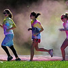 Pat Christman <br /> Runners leave a cloud of color as they pass through a color station during Saturday's race.