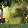 Pat Christman <br /> A volunteer throws yellow dye at runners Saturday.