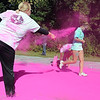 Pat Christman <br /> Crystal Berg makes sure the back of a runner's shirt gets covered in pink dye Saturday.