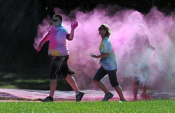 Pat Christman <br /> A pink cloud follows a pair of runners after passing through a color station near the end of Saturday's Color Rush.