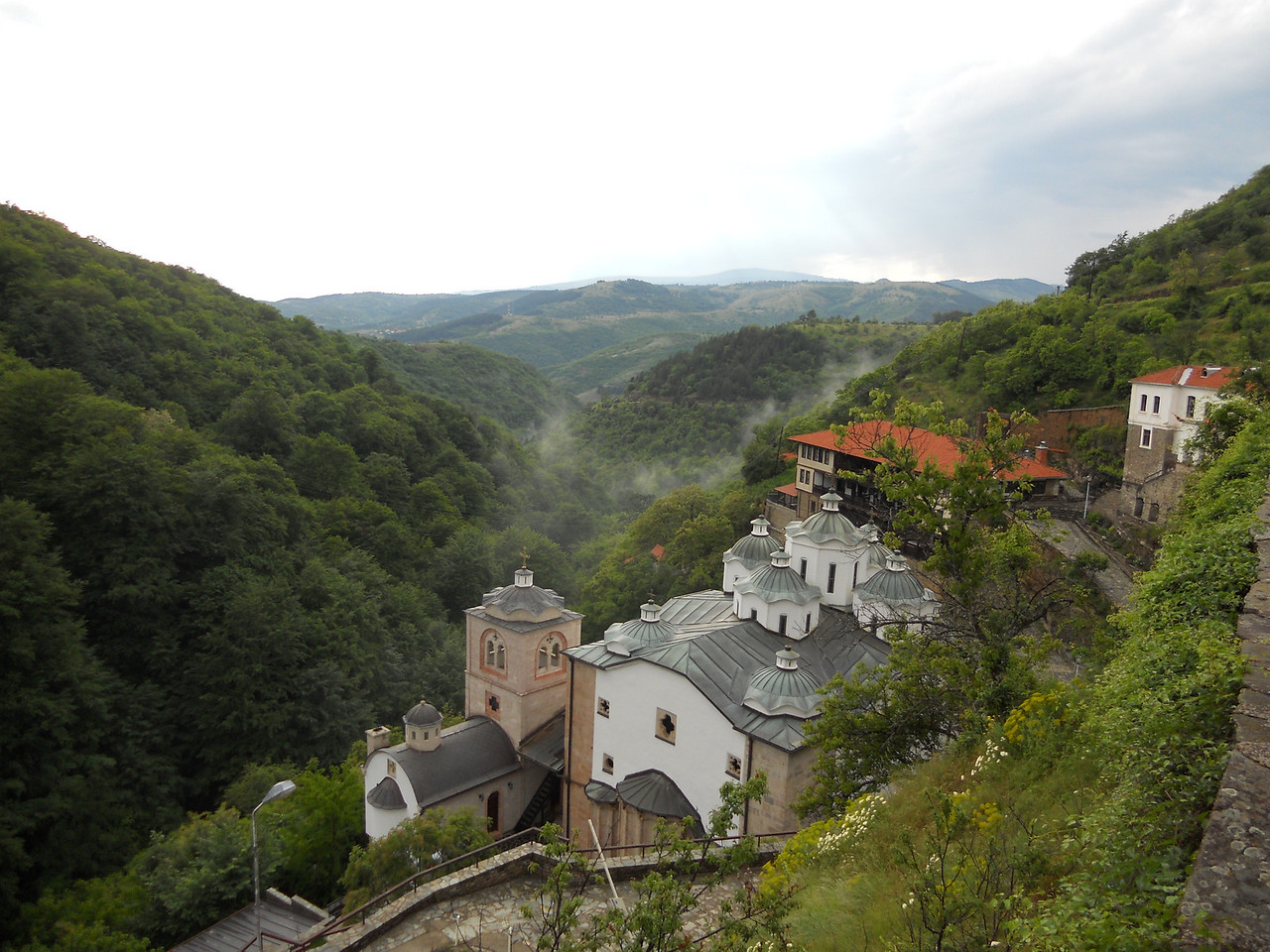 The monestary has a stunning location in the mountains, with atmospheric mist swirling around it.