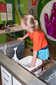 Rachel holding her hand in ice water to get  a wax casting made.