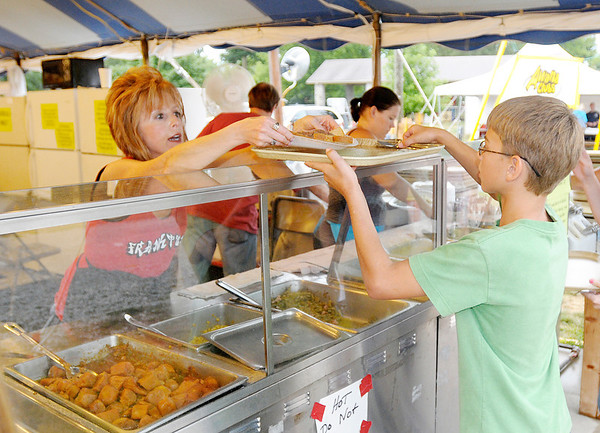 Trudy Caldwell hands Damien Shields, 12, his Beef Manhattan at The Christian Congregation food tent during the 4-H Fair on Wednesday. The tent has been a regular at the fair for 50 plus years and the most popular item on the menu is the Chicken and Noodles, said Paula Trissel.
