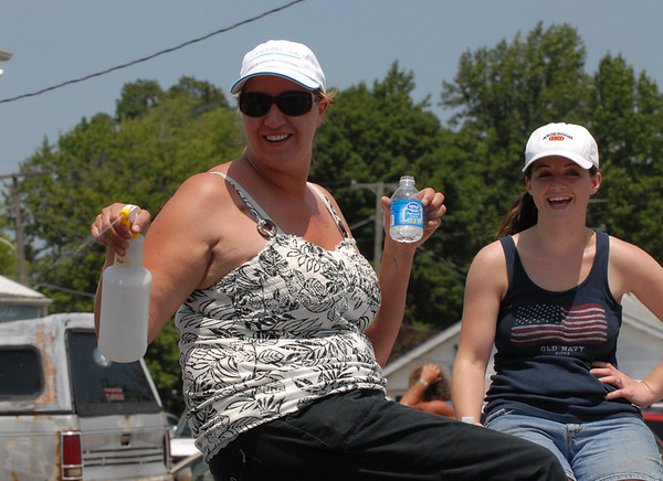 A woman riding a float sprays water on people watching the parade.