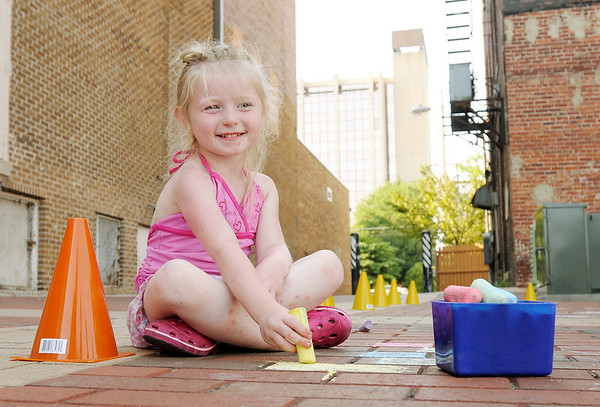 Brianna Oliver, 5, colors brick pavers with chalk during the Freedom Fest at Town Center Park on Wednesday. The event was sponsored by Celebration Church at Arrow Heights, Madison Park Church of God and South Meridian Church of God.