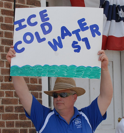 Mike Shively holds up a sign for ice cold water at $1 a bottle.